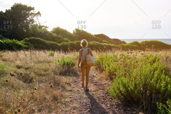 Blonde woman on her back walking along a coastal path with a wicker basket as the sun rises