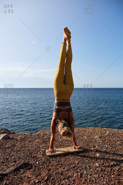 Vertical photo of a woman in yellow tights practicing handstand yoga with her feet up and her hands resting on a wooden board in front of the sea