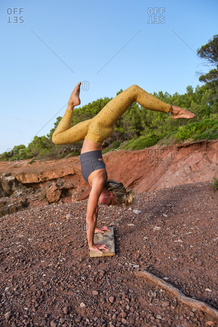 Vertical photo of a woman in sport clothes practicing handstand yoga with her feet up and the legs open and her hands resting on a wooden board on a path in the middle of the forest