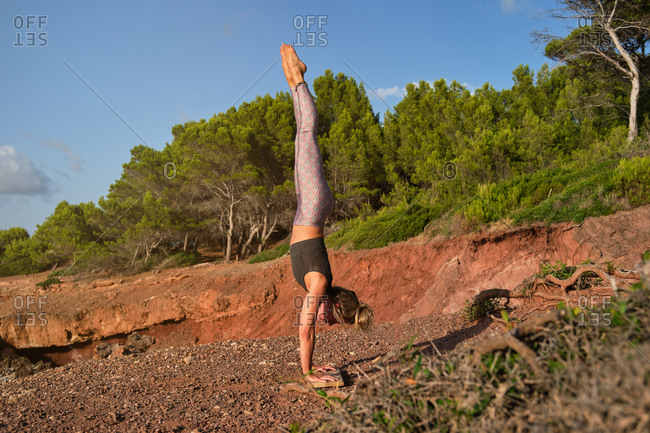 Woman in tights practicing handstand yoga with her feet up and her hands resting on a wooden board on a path in the middle of the forest