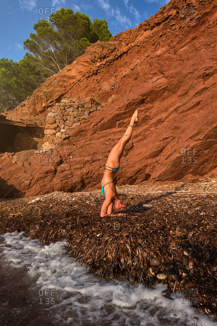 Vertical photo of a woman in a swimsuit doing a variation of the Handstands yoga pose on a beach in the middle of a forest