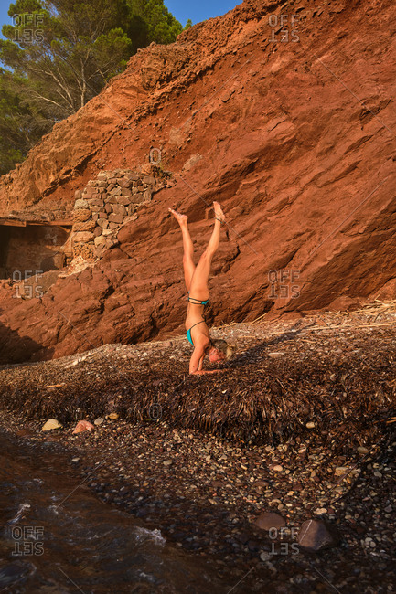 Vertical photo of a blonde woman in a swimsuit doing the Handstands yoga position on a beach in the middle of a forest