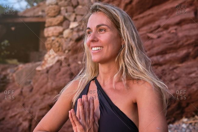 Portrait of a blonde woman in a swimsuit meditating with her hands together on a beach in the middle of the forest