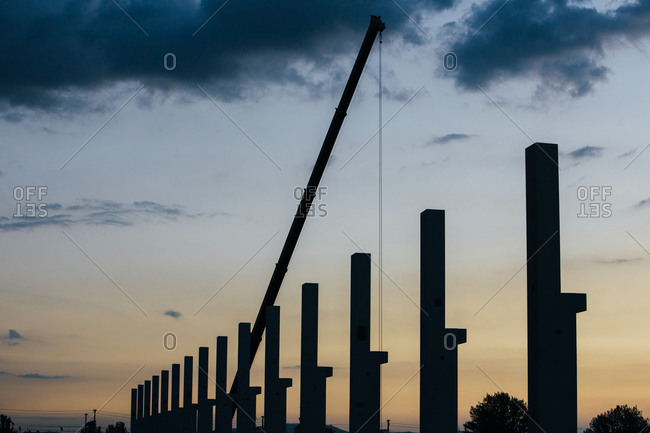 Silhouette of construction site with cranes and pillars at sunset