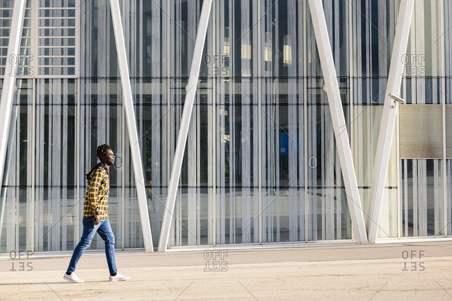 Young black man passing in front of a modern office building, lifestyle concept