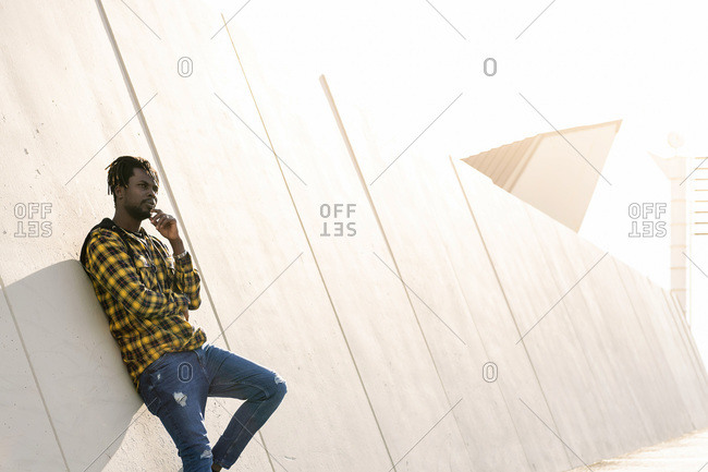Young black man leaning against a modern concrete structure at sunset, lifestyle concept