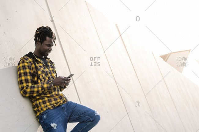 Smiling young black man writing a message on his phone leaning on a modern concrete structure, concept of lifestyle and technology