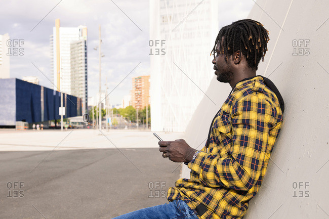 Young african man with his phone leaning on a modern concrete structure at the city, concept of lifestyle and technology