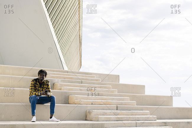 Young black african american man sitting on a concrete staircase with his phone, concept of lifestyle and technology