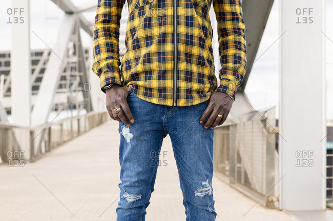 Central body part of an unrecognizable young black man with his hands in his pockets, lifestyle concept