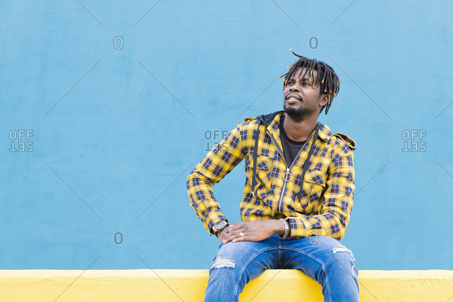 Smiling black man sitting on a yellow wall with a blue wall as a background, lifestyle concept