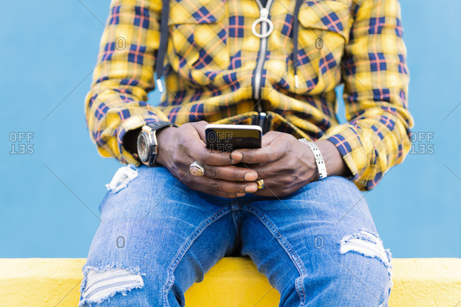 Hands of an unrecognizable black man writing a message on his mobile phone sitting on a yellow wall with a blue wall in the background, technology and lifestyle concept