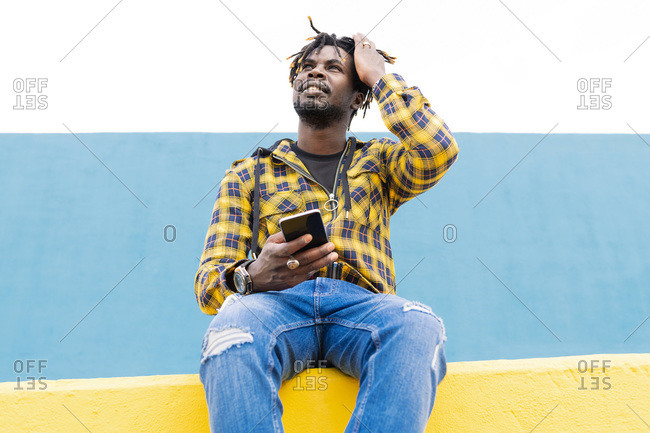 Smiling black man sitting on a yellow wall with a smart phone at his hand, concept of technology and lifestyle