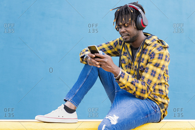 Young african man with headphones sitting on a yellow wall consulting his smartphone with a blue wall in the background, technology and lifestyle concept