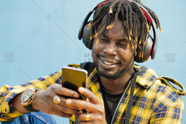 Portrait of a young black man with a headphones writing on his smart phone with a blue wall in the background, technology and lifestyle concept