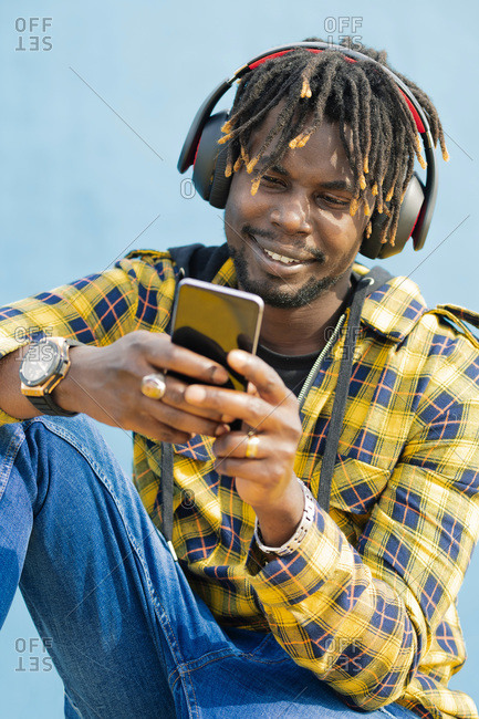 Vertical portrait of a young black man with a headphones writing on his smart phone with a blue wall in the background, technology and lifestyle concept