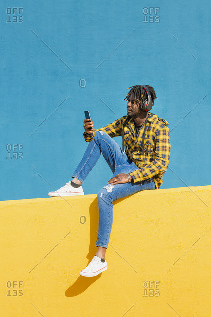 Young black man sitting on a yellow wall with headphones consulting his smart phone with a blue wall in the background, technology and lifestyle concept