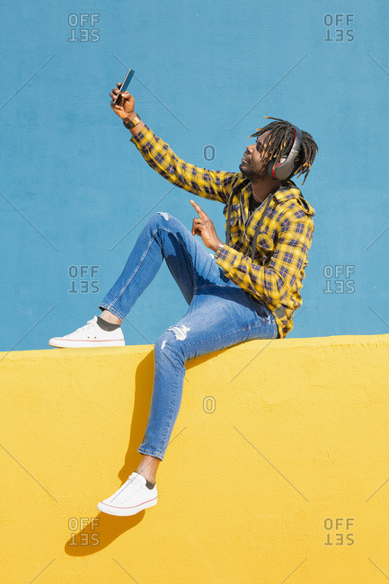 Young black man sitting on a yellow wall with headphones making a video call with his smart phone with a blue wall in the background, technology and lifestyle concept
