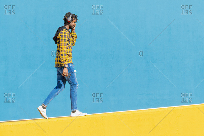 Young black man with headphones walking along a yellow wall and a blue wall in the background with his smartphone in his hand, technology and lifestyle concept