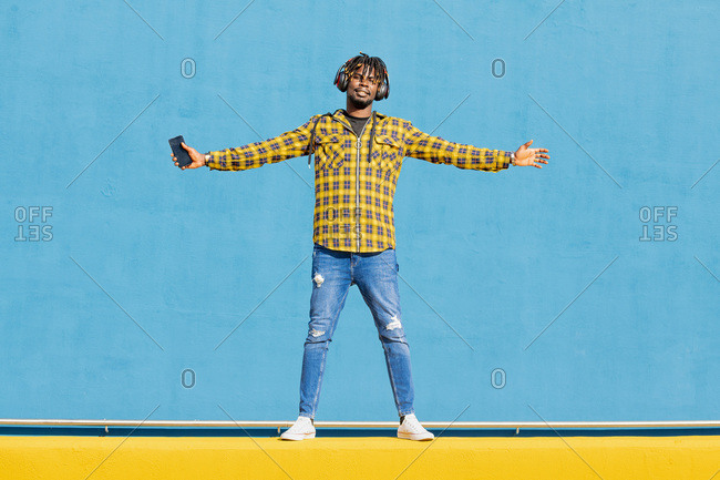 Attractive young black man listening to music from his phone with a large headphone on a blue background, technology and lifestyle concept