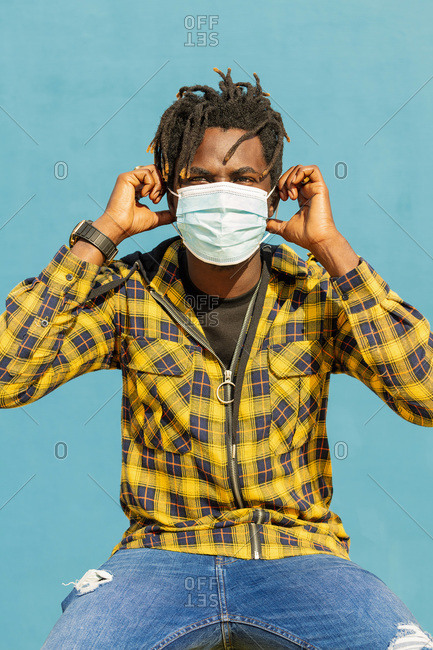 Vertical photo of an attractive young black man wearing a protective mask, lifestyle concept and covid protection
