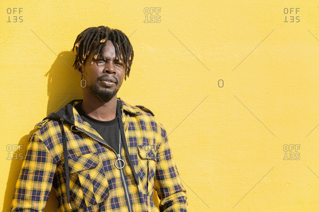 Attractive young african man leaning against an intense yellow wall, lifestyle concept