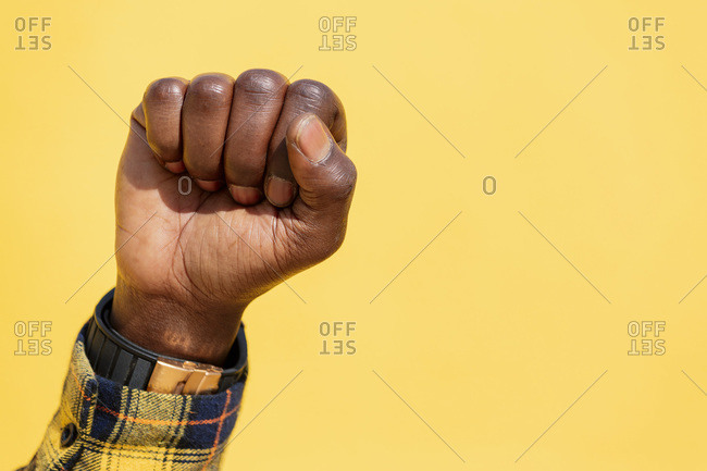 Raised fist of a black man on an intense yellow background, concept of human rights struggle and lifestyle