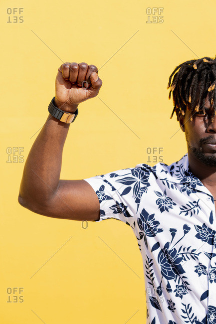 Vertical photo of an attractive young black man with raised fist on an intense yellow background, concept of human rights struggle and lifestyle