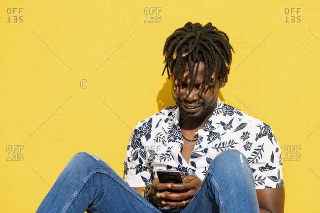 Smiling young black man sitting against a yellow wall consults his smartphone, technology and lifestyle concept