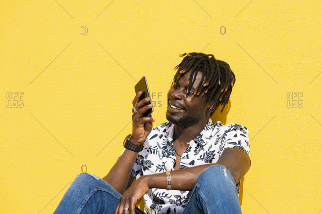 Smiling young black man sitting against a yellow wall recording a voice message with his smartphone, technology and lifestyle concept