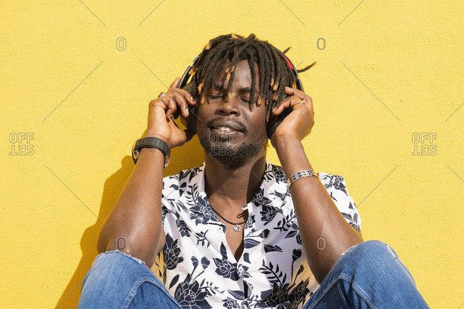 Young black man sitting against a yellow wall listening and enjoying music with large headphones, technology and lifestyle concept