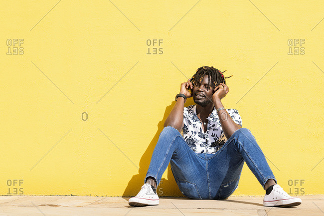 Attractive young black man sitting against a yellow wall listening and enjoying music with large headphones, technology and lifestyle concept