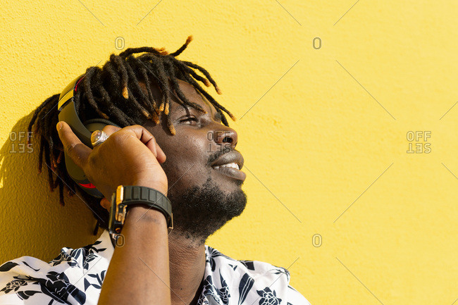 Smiling young african man listening to and enjoying music with large headphones on yellow background, concept of technology and lifestyle