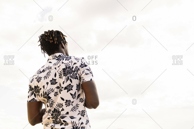 Back view of a stylish young african american man in a flower shirt with the sky in the background, concept of freedom and lifestyle