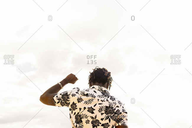View from the back of a stylish young black man with his fist raised and the sky in the background, concept of freedom and struggle for the defense of human rights