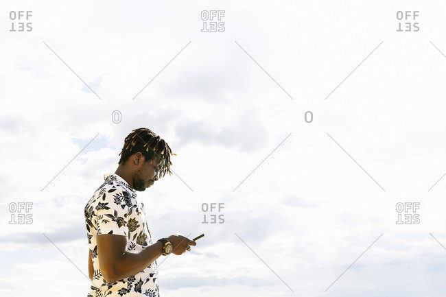 Stylish young black man looking at his mobile phone with the sky in the background, technology and lifestyle concept