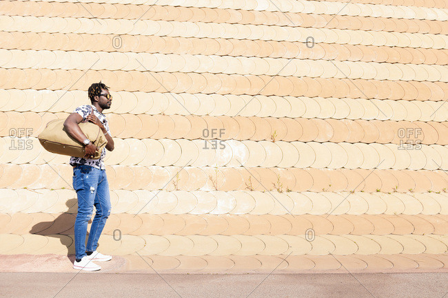 Stylish young black man with sunglasses and a large travel bag, concept of freedom and traveler lifestyle