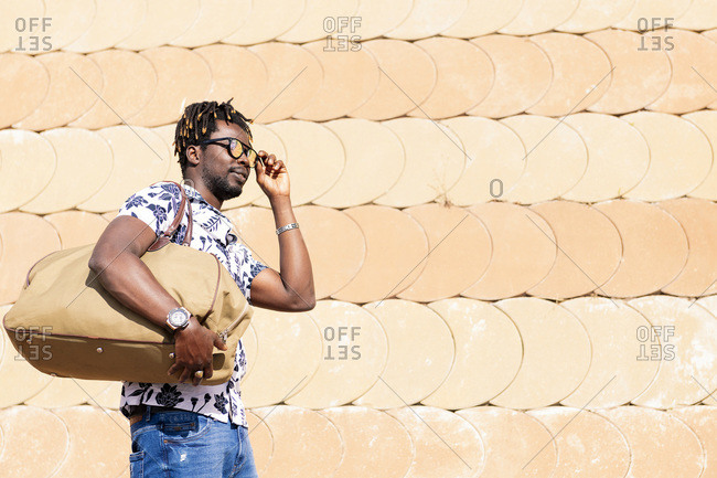 Portrait of a stylish young black man with a large travel bag that fits his sunglasses, concept of freedom and traveler lifestyle