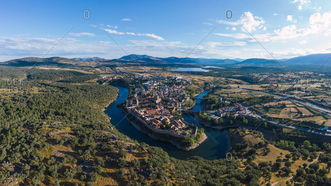 Spectacular scenery of old town of Buitrago del Lozoya and river under cloudy sky on sunny day