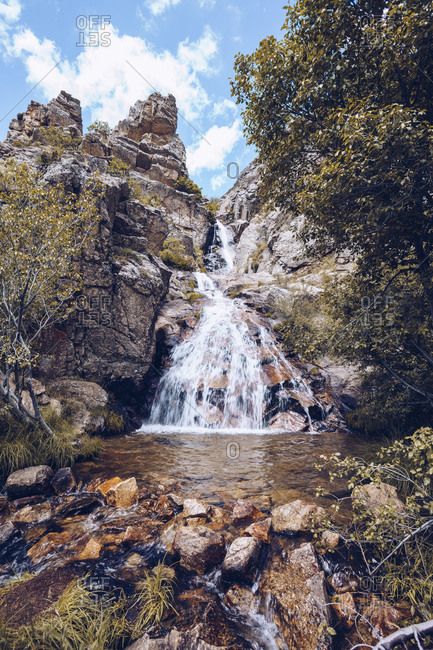 Low angle of wonderful scenery of waterfall in forest in highland area on background of blue cloudy sky in Buitrago del Lozoya