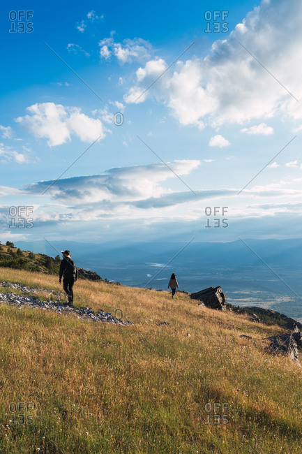 Travelers walking on hill and admiring amazing view of mountains and valley on sunny day