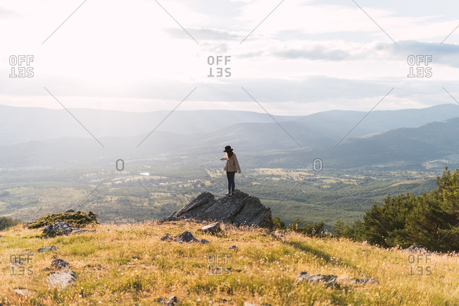 Woman traveler standing on rough stone and admiring amazing view of mountains and valley on sunny day