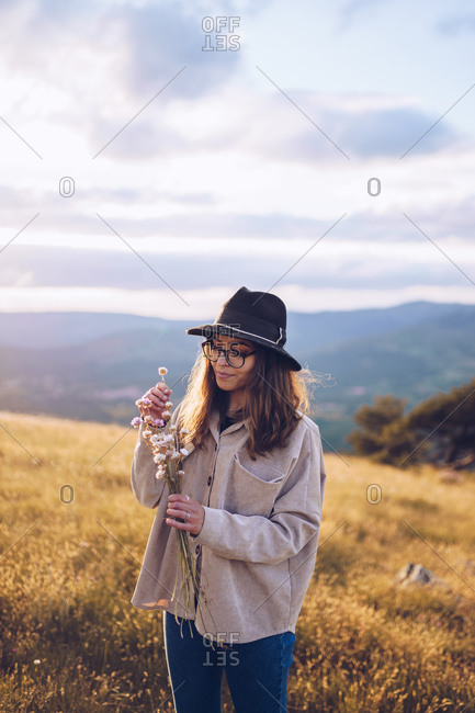 Tender female with bouquet of wildflowers standing on hill on background of majestic mountainous landscape in autumn during sundown