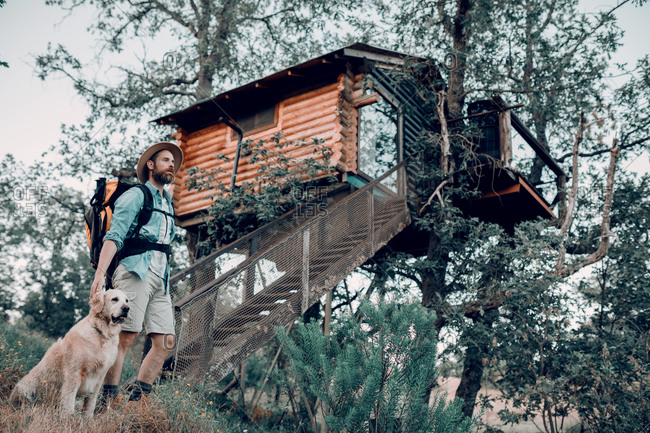 Happy male traveler with backpack walking in the forest with friendly dog in a cabin house on tree