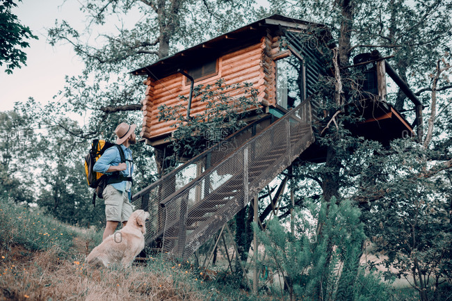 Low angle side view of unrecognizable male traveler with backpack walking in the forest with friendly dog in a cabin house on tree