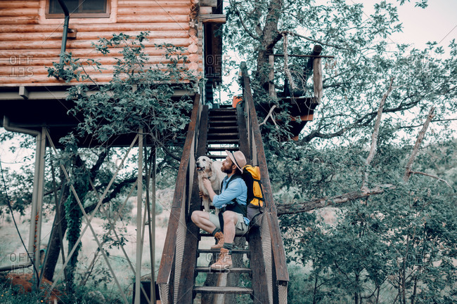 Male tourist with backpack sitting on wooden steps of tree house and stroking fluffy dog during vacation in forest