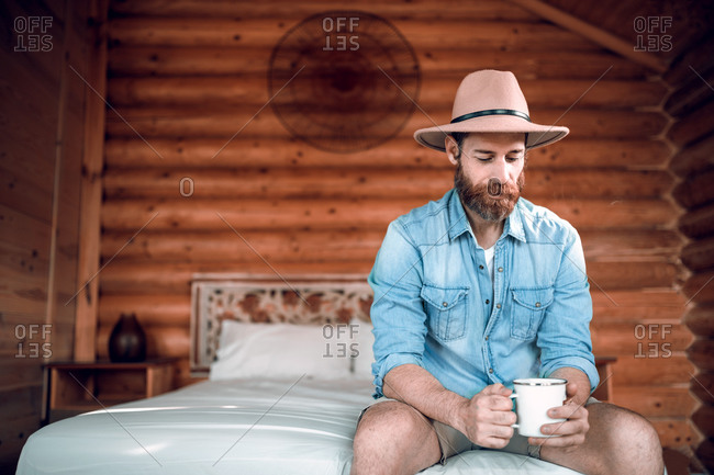 Relaxed traveling male in casual wear sitting on comfortable bed in wooden house and enjoying fresh coffee in morning