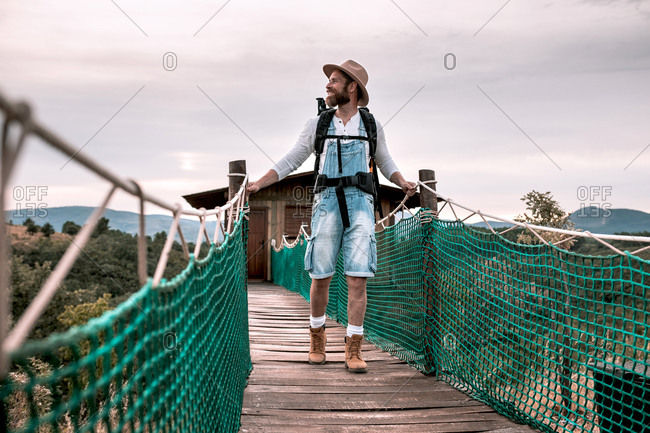 Content male tourist with backpack walking along suspension bridge and admiring amazing landscape during vacation in summer