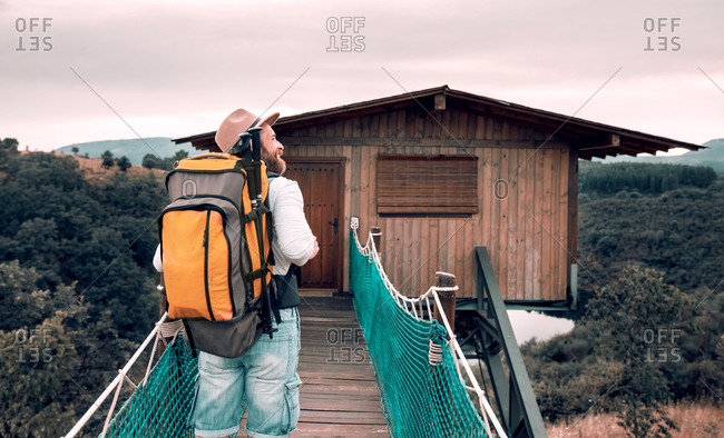 Back view of unrecognizable content male tourist with backpack walking along suspension bridge and admiring amazing landscape during vacation in summer
