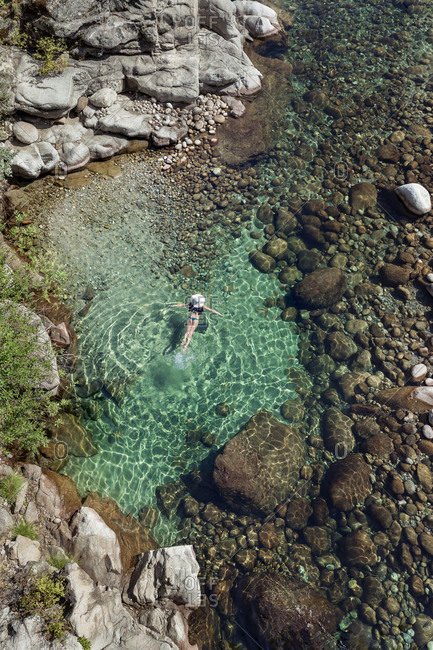 From above aerial view of slim female in swimwear swimming in transparent water near stony shore on resort